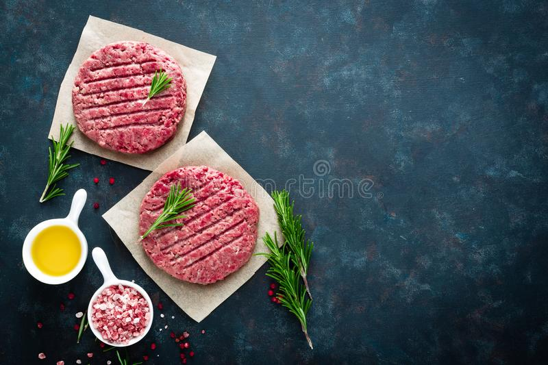 Fresh minced beef meat burgers with spices on dark background. Raw ground beef meat. Flat lay. Top view royalty free stock photo