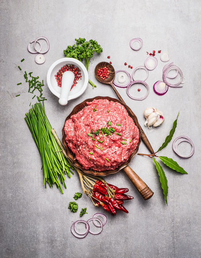 Fresh Minced meat with green seasoning and ingredients for tasty cooking on gray stone background. Top view composing royalty free stock photos