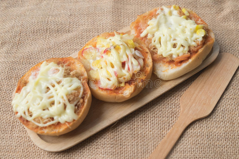 Fresh mini buns topped with pizza. On wooden tray stock image