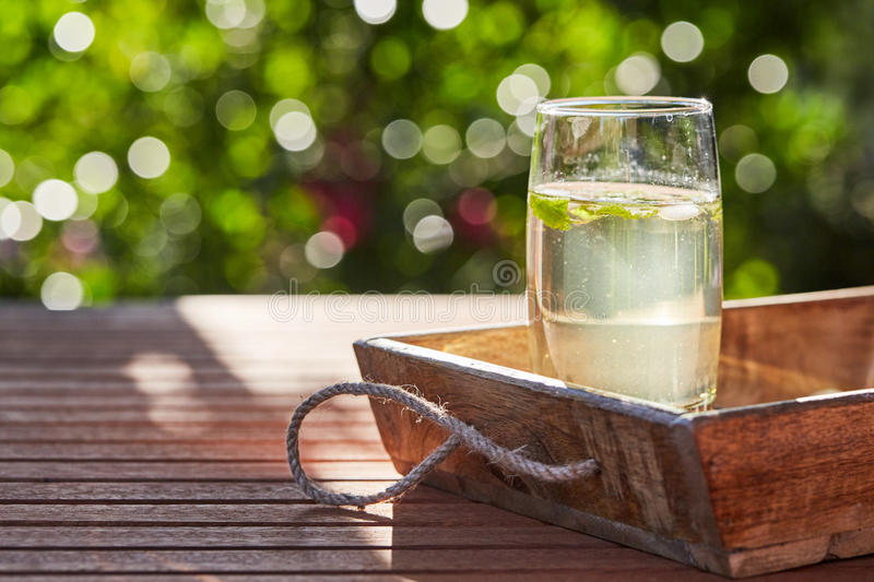 Fresh mint drink with ice in a glass on a wooden table stock photography