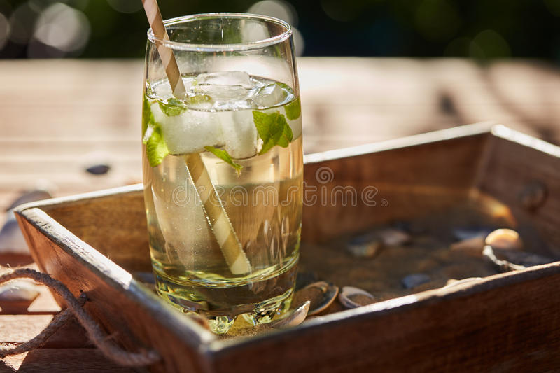 Fresh mint drink with ice in a glass on a wooden table royalty free stock photo