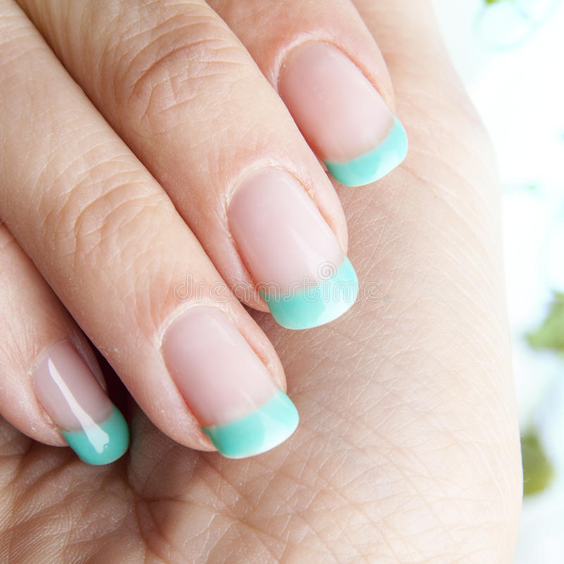 Fresh mint nails design. Female nails with beautiful manicure design and fresh mint leaves on background stock photography