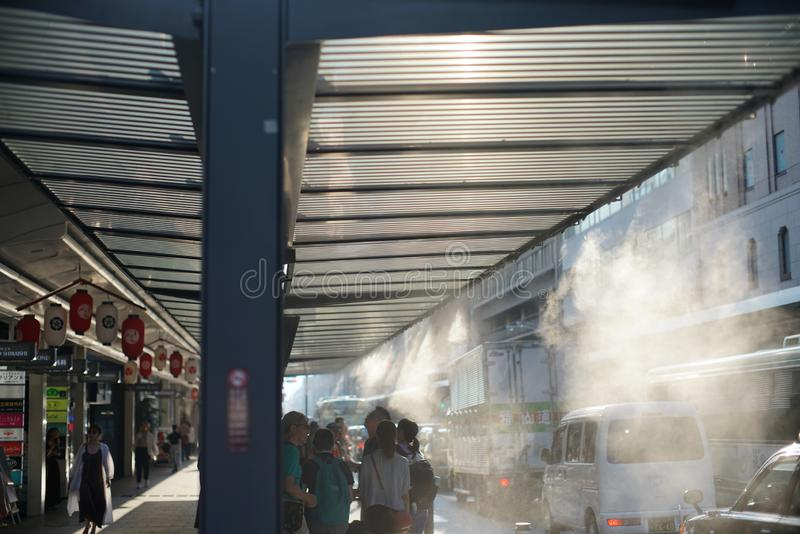 Fresh mist shower at Shijo Takakura bus stop on hot summer days. Kyoto,Japan-July 30,2019: Fresh mist shower at Shijo Takakura bus stop on hot summer days stock image