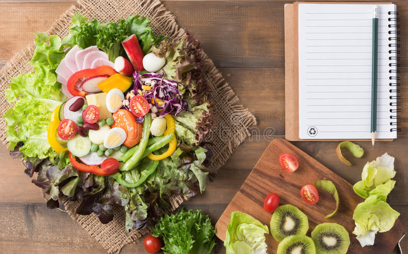 Fresh mix vegetation salad on brown wood background. With notebook and pencil, concept diet and healthy food royalty free stock photography