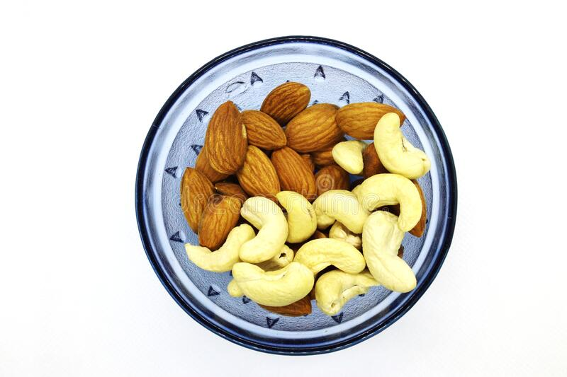 Fresh Mixed Almonds and Cashew nuts in a blue bowl, Top view. White isolated background royalty free stock photography