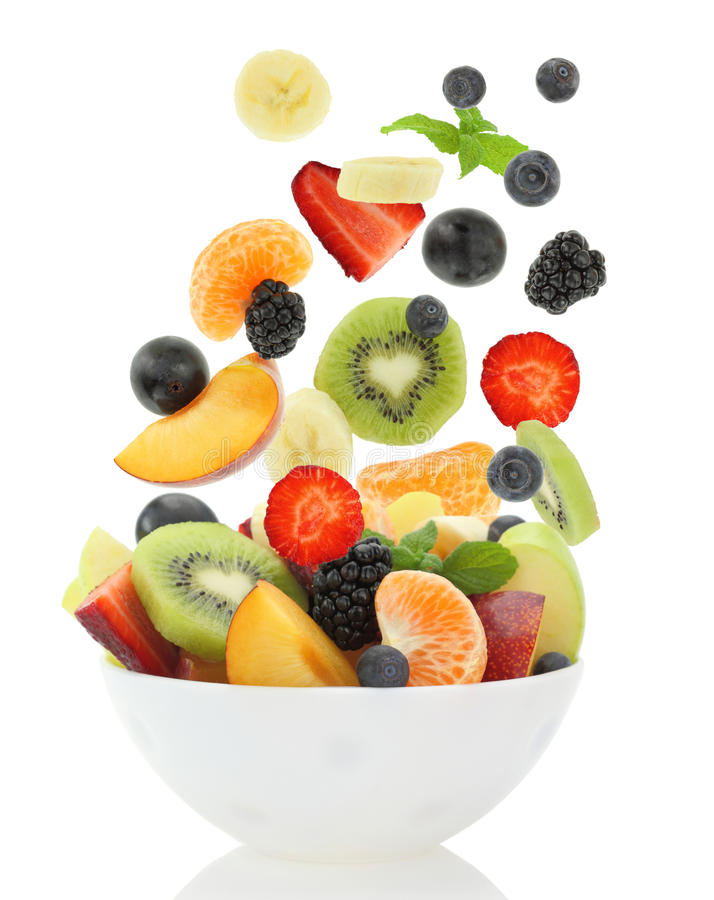 Fresh mixed fruit salad falling into a bowl of salad royalty free stock photography