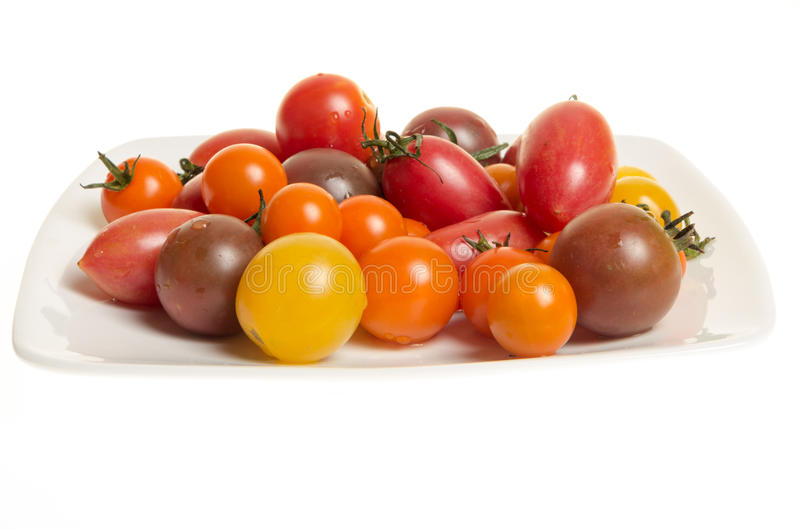 Fresh mixed tomatoes on white plate royalty free stock photo
