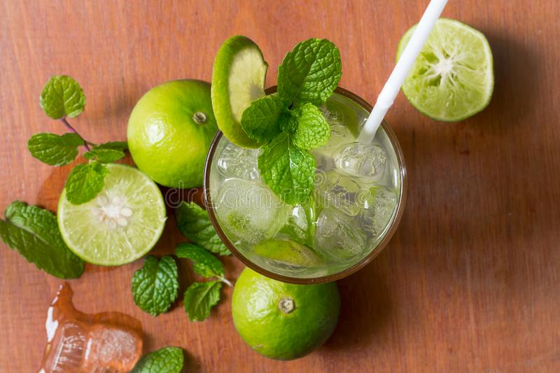 Fresh Mojito cocktail with fresh green limes, mint and ice on wooden background. stock photos