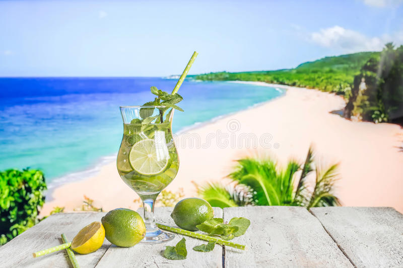 Fresh mojito cocktail. On white wooden table with blue sea as a background royalty free stock image