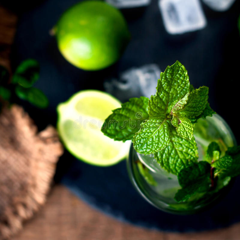 Fresh mojito drink coctail with lime and mint in a glass on bla. Ck stone board and wooden rustic table royalty free stock images