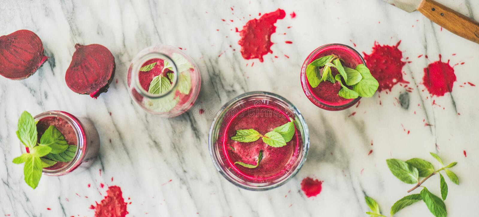 Fresh morning beetroot smoothie or juice in glasses, marble background royalty free stock image