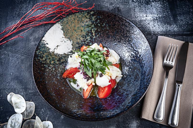 Fresh Mozzarella salad with tomato, seasoned with sage pesto and white sauce. Top view, flat lay food with copy space. Italian stock photos