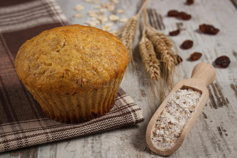 Fresh muffin with oatmeal, rye flour and ears of rye grain, delicious healthy dessert royalty free stock photo