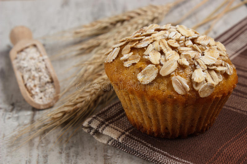 Fresh muffin with oatmeal, rye flour and ears of rye grain, delicious healthy dessert royalty free stock images