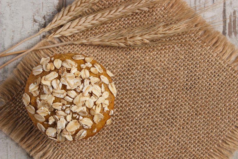 Fresh muffins with oatmeal and ears of rye grain, delicious healthy dessert, copy space for text on jute canvas stock image
