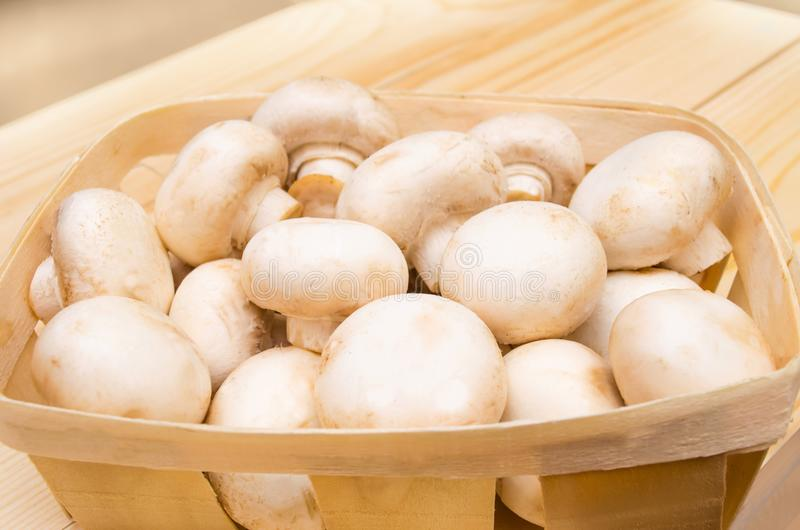 Fresh mushrooms champignons in a basket on a wooden background royalty free stock photography