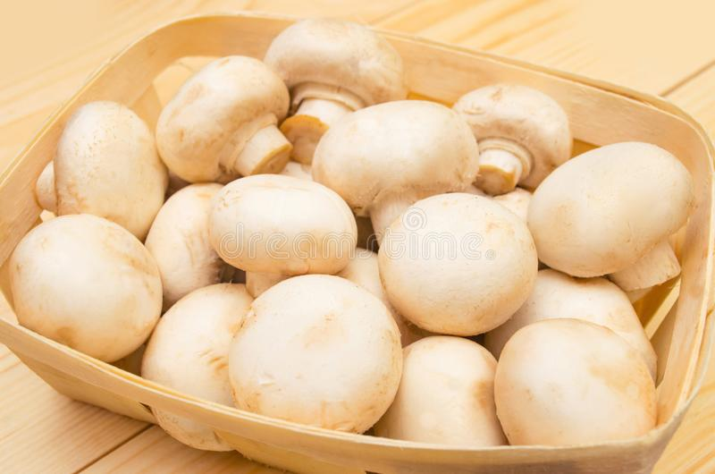 Fresh mushrooms champignons in a basket on a wooden background stock photography