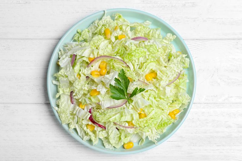 Fresh napa cabbage salad served on white table, top view. Fresh napa cabbage salad served on white wooden table, top view stock image
