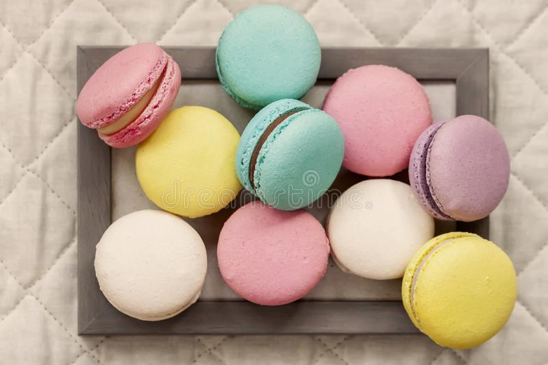 Fresh natural colorful macarons of different tastes in wooden frame on light napkin, top view, unusual abstract sweet stock images
