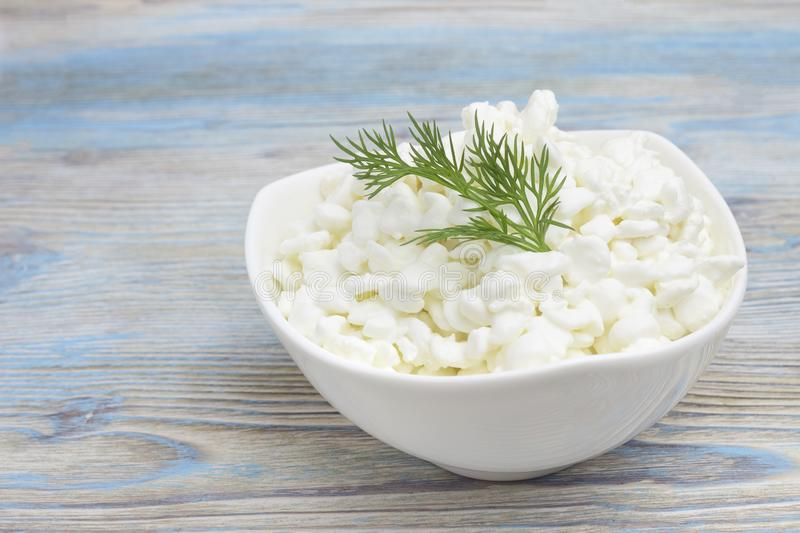 Fresh natural cottage cheese in a white ceramic bowl on the blue wooden table. Green dill. Organic eco healthy meal, dairy product stock photos