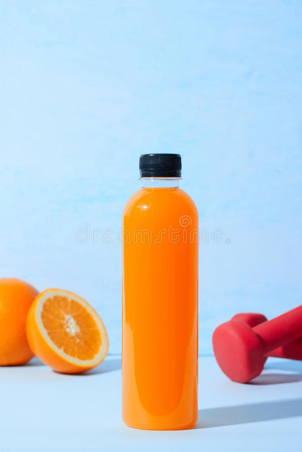 Fresh natural orange juice with dumbbells on table. Healthy drink. royalty free stock image
