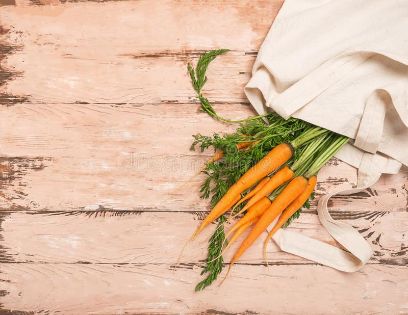 Fresh natural organic carrot bag made of cotton wooden rustic background. Natural organic products. Ecology concept. royalty free stock photography