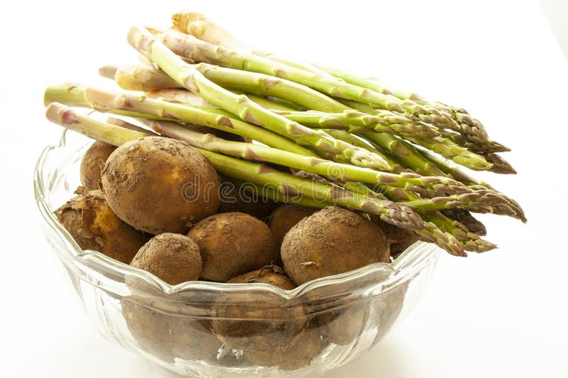 Fresh new potatoes with peel on and green asparagus in a glass bowl. Close up image on white background stock photos