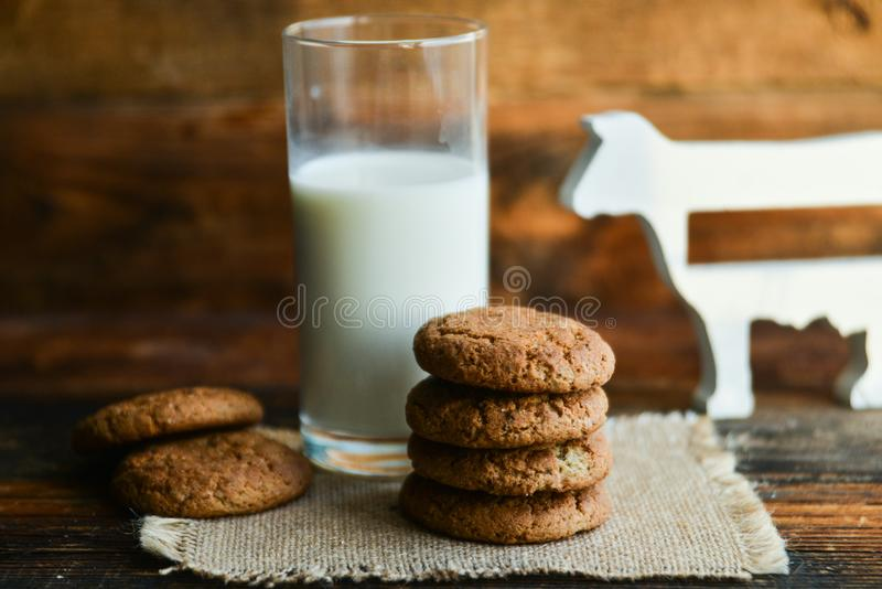 fresh oatmeal cookies and milk on wooden background with spikes of oats royalty free stock photos