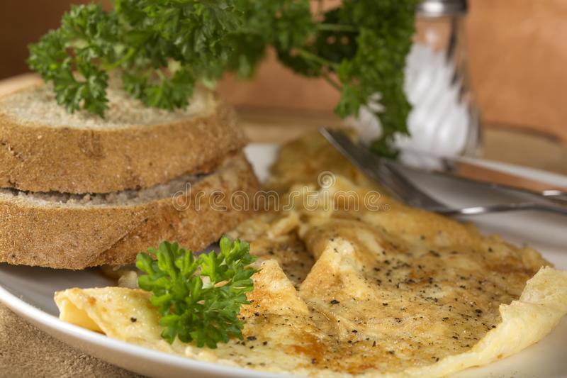 Fresh omelette with ground black pepper and parsley on plate. With bread stock photos