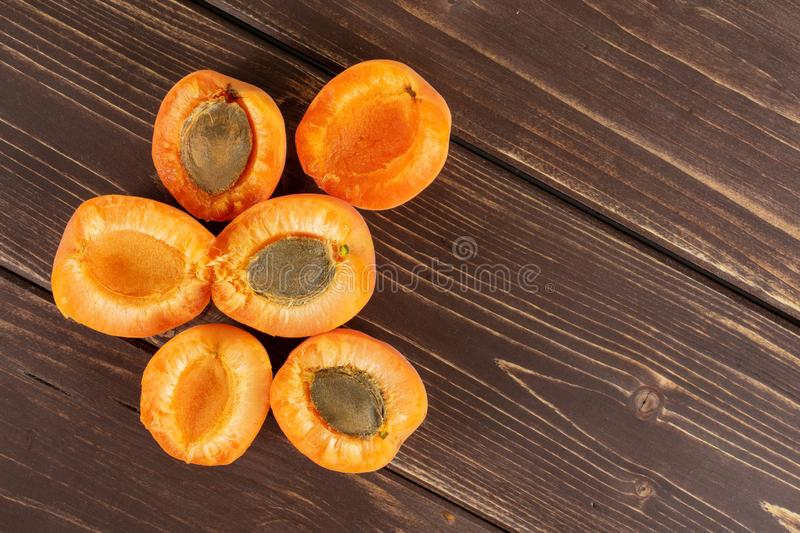 Fresh orange apricot on brown wood. Group of six halves of velvety fresh deep orange apricot with a stone flatlay on brown wood royalty free stock photography