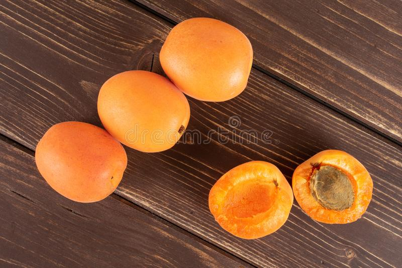 Fresh orange apricot on brown wood. Group of three whole two halves of fresh deep orange apricot with a stone flatlay on brown wood stock photography