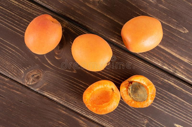 Fresh orange apricot on brown wood. Group of three whole two halves of fresh deep orange apricot with a stone flatlay on brown wood stock photo