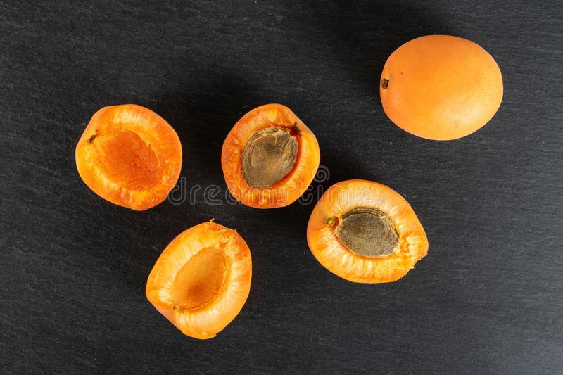 Fresh orange apricot on grey stone. Group of one whole four halves of fresh deep orange apricot with a stone flatlay on grey stone stock images