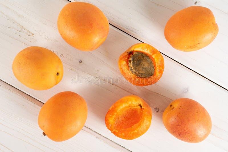 Fresh orange apricot on grey wood. Group of five whole two halves of fresh deep orange apricot with a stone flatlay on white wood stock image