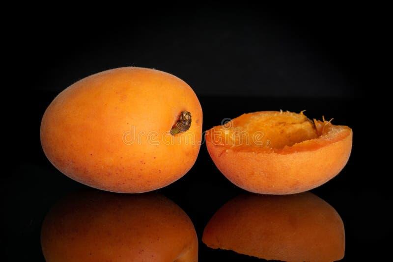 Fresh orange apricot isolated on black glass stock image
