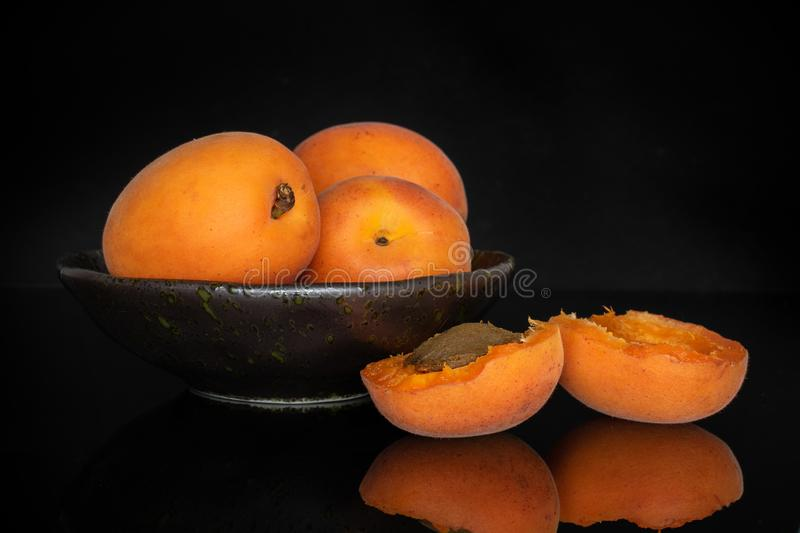 Fresh orange apricot isolated on black glass. Group of three whole two halves of fresh deep orange apricot on grey ceramic plate with a stone isolated on black stock photos