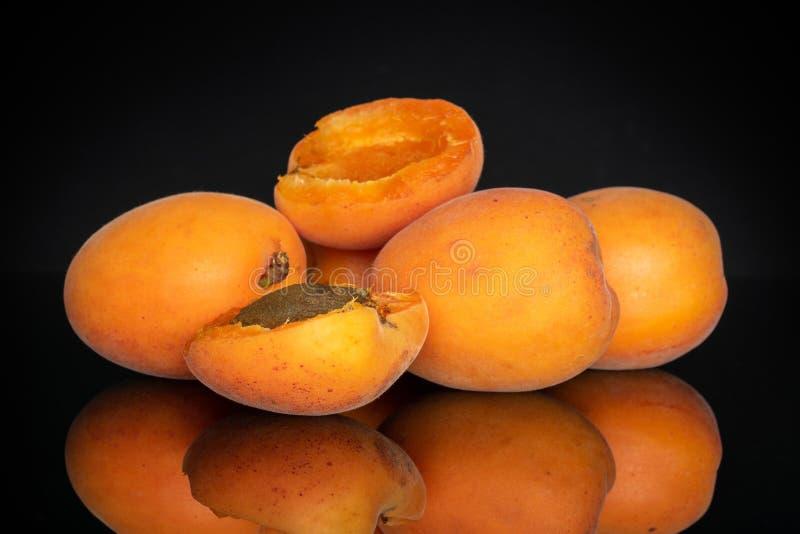 Fresh orange apricot isolated on black glass. Group of three whole two halves of fresh deep orange apricot with a stone isolated on black glass stock photo