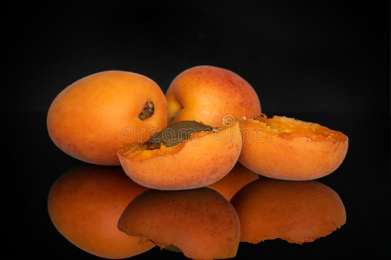 Fresh orange apricot isolated on black glass. Group of two whole two halves of fresh deep orange apricot with a stone isolated on black glass royalty free stock image