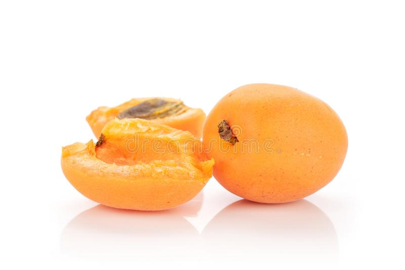 Fresh orange apricot isolated on white. Group of one whole two halves of fresh deep orange apricot with a stone isolated on white background royalty free stock photography