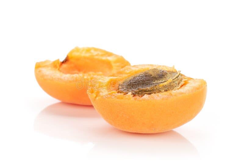 Fresh orange apricot isolated on white. Group of two halves of fresh deep orange apricot with a stone isolated on white background royalty free stock photography