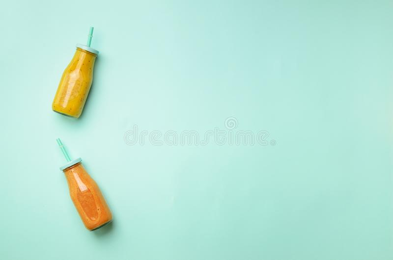 Fresh orange, banana, pineapple, mango smoothies and juicy fruits on blue background. Detox summer drink. Vegetarian concept. Top royalty free stock images