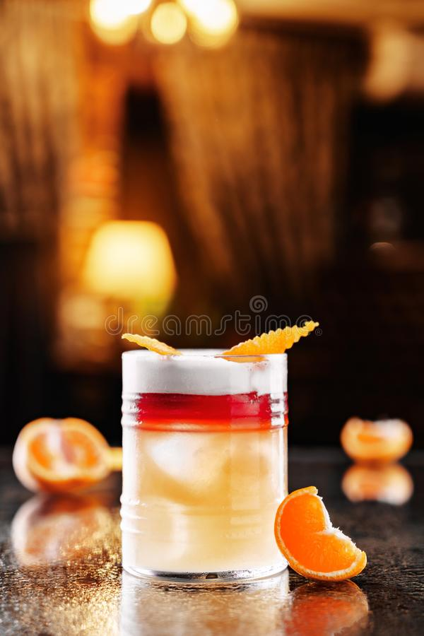 Fresh orange drink with vodka, tangerines and ice in glass on backdrop of the restaurant atmosphere. Summer drinks and cocktails stock image
