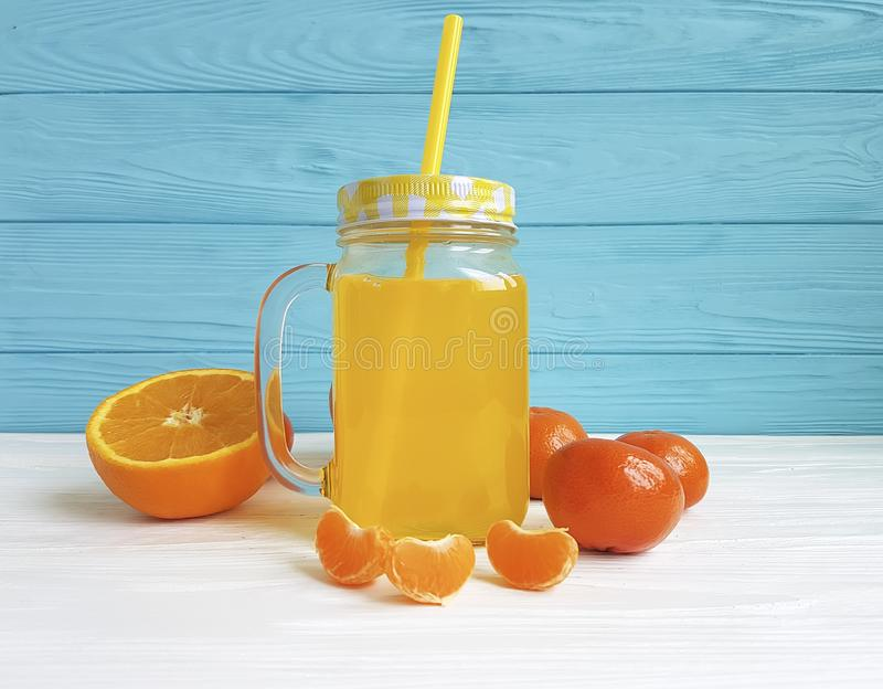 Fresh orange fresh clear kitchen glass with straw morning white and blue wooden, mandarins. Fresh orange fresh clear glass morning straw from white and blue royalty free stock image