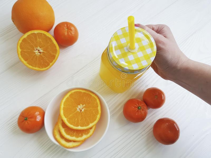 Fresh orange lemonade hand fresh tangerine morning clear glass with a tube of white wooden. Fresh orange fresh clear glass tube of white wooden morning healthy royalty free stock photography