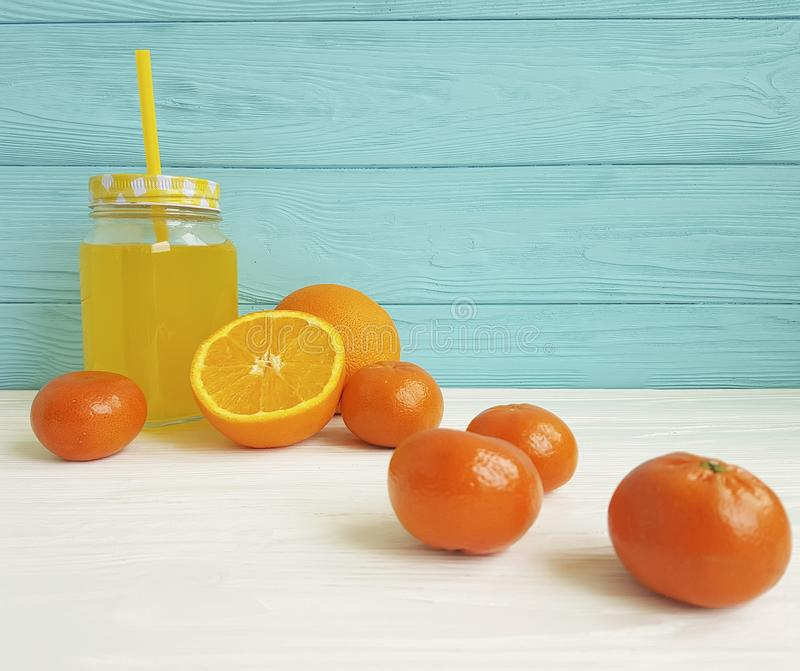Fresh orange fresh clear kitchen tasty with straw morning white and blue wooden, mandarins. Fresh orange fresh clear morning straw from white and blue wooden royalty free stock photography