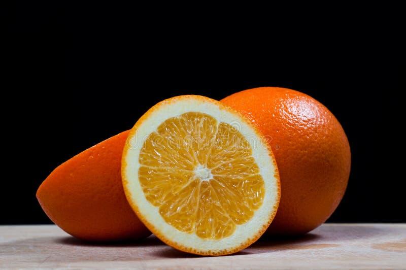 Fresh orange fruit. On a black background royalty free stock photos