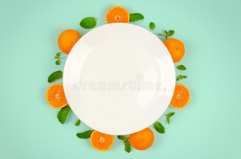 Fresh orange fruits and mint leaves on top view with white plate and pastel green color background for healthy food concept royalty free stock photos