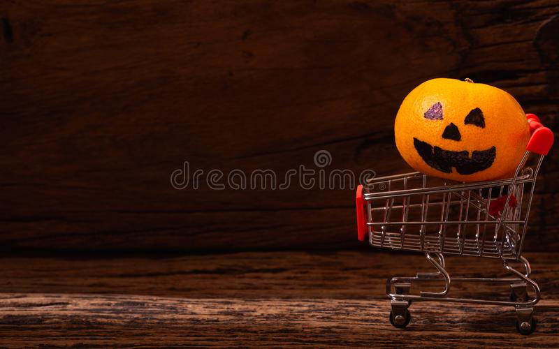 Fresh Orange with Halloween Pumpkins painted face on shopping ca stock image