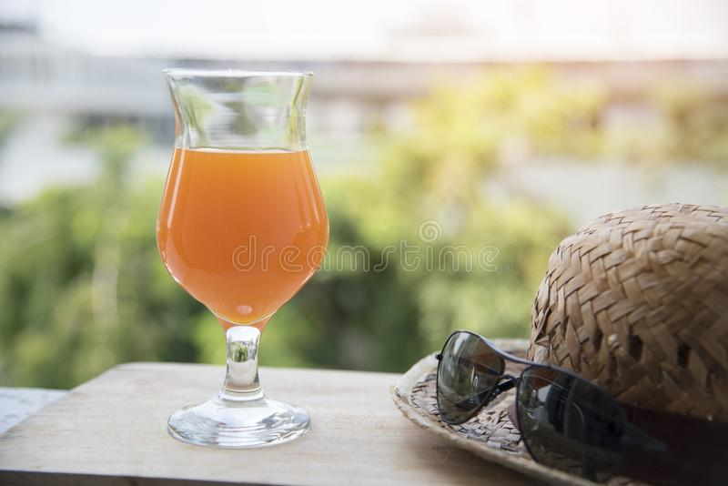 Fresh orange juice on the beach with blue sky background and sea bokeh , summer concept.  stock images