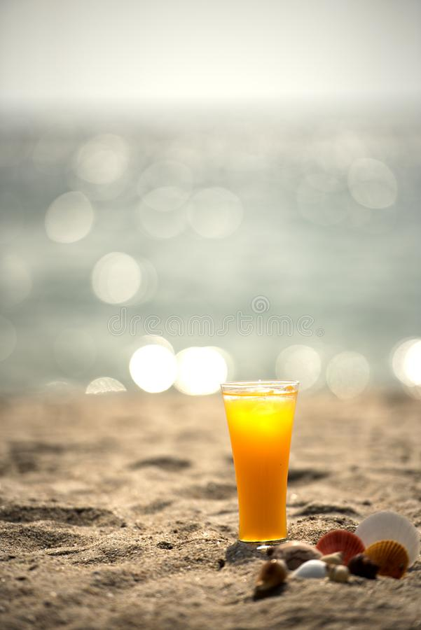 Fresh orange juice on the beach with blue sky. Background and sea bokeh , summer concept royalty free stock images